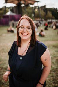 Autorin Babsi Schwarz auf einer Wiese. Sie trägt ein dunkles Shirt und eine Kette, ihre braunen Haare sind offen und sie lacht. Im Hintergrund sitzen einige Leute auf einer Wiese